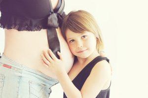 dziecko obejmujące brzuch ciężarnej mamy